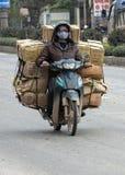 Kaufmann transportiert viele Kästen auf der Rückseite des Motorrades Stockfotos