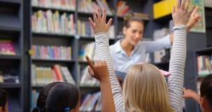 Kaukascy żeńskiego nauczyciela nauczania schoolkids w szkolnej bibliotece 4k zbiory wideo