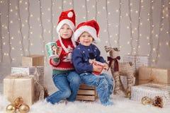 Kaukascy dzieci brat i siostra siedzi w pulowerach wpólnie ściskający odświętność nowego roku lub boże narodzenia zdjęcia royalty free