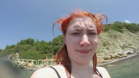 Kaukascy szczęśliwi śmieszni miedzianowłosi dziewczyn spojrzenia w kamera obiektyw przeciw tłu denna i piaskowata stroma zieleni  zbiory