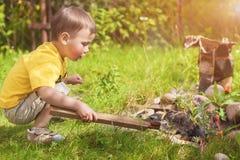 Kaukasier Little Boy, das draußen Feuer nahe Firepace beschäftigt Stockbild