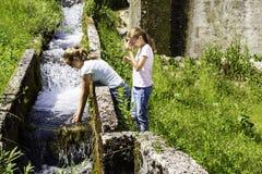 Kaukasisch-aussehende Jugendliche spielen mit einem Gebirgsstrom in Zabljak Montenegro an einem sonnigen Tag lizenzfreie stockbilder