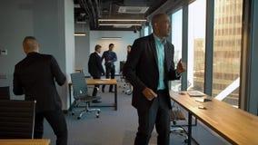 Kaukasisch en Afrikaans Amerikaans zakenlui die op mede-werkt kantoor dansen stock videobeelden