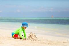 Kaukasisch jongen de bouwzandkasteel op tropisch strand royalty-vrije stock fotografie