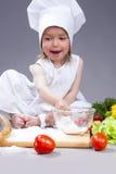 Kaukasisch Meisje in Cook Uniform Preparing Courses met Bloem en Groenten in Studio stock foto