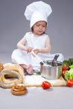 Kaukasisch Meisje in Cook Uniform Preparing een Soep en het Maken van een Mengsel met Lepel stock afbeeldingen