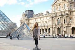 Kaukasisch meisje grijze laag dragen en zich dichtbij Louvre bevinden en glaspiramide die in Parijs Royalty-vrije Stock Foto's