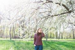 Kaukasisch meisje met lang bruin haar in de bloeiende tuin Het meisje is gekleed in een kleur van jasjemarsala en een bruine sjaa Stock Fotografie