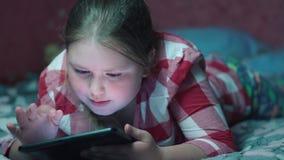 Kaukasisch meisjes speelspel op tablet en het liggen op de bank in de avond stock video