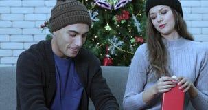 Kaukasisch paar die een gift scheeftrekken stock footage