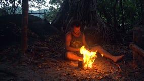 Kaukasisch Savage Man Burning Little Campfire in het Tropische Bos bij Schemering om Ketel met Rijst voor Diner te koken stock videobeelden