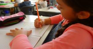 Kaukasisch schoolmeisje die bij bureau in een klaslokaal op school 4k bestuderen stock videobeelden
