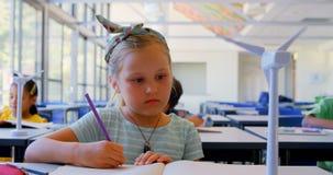 Kaukasisch schoolmeisjenotitieboekje bij bureau in klaslokaal 4k stock videobeelden