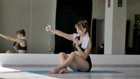 Kaukasisch sportenmeisje in sporten eenvormige foto's zelf op de telefoon stock videobeelden