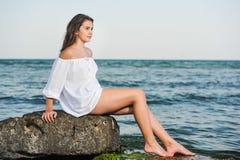 Kaukasisch tienermeisje in bikini en het witte overhemd lounging op lavarotsen door de oceaan Royalty-vrije Stock Foto