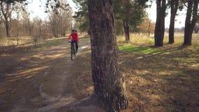 Kaukasisch van de de vrouwensport van de sportfietser off-road de fietspark dichtbij boom Een vrouwelijke atleet in sportinvnoy k stock videobeelden