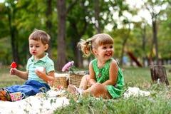 Kaukasisch weinig jongen en meisje die snoepjes eten Stock Afbeeldingen