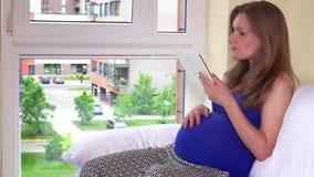 Kaukasisch zwanger meisje die de zitting van de tabletcomputer gebruiken dichtbij venster stock footage