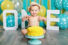 Kaukasische babyjongen die zijn eerste verjaardag vieren Cakeineenstorting royalty-vrije stock foto's