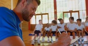 Kaukasische basketbalbus die op klembord in basketbalhof 4k schrijven stock video