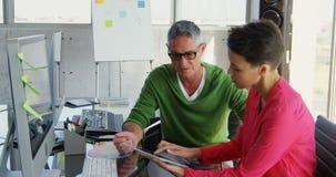 Kaukasische Bedrijfsmensen die over digitale tablet bij bureau in bureau 4k bespreken stock videobeelden