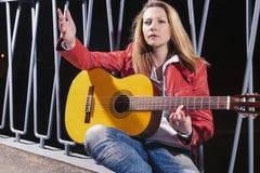 Kaukasische blonde Frau, die in der roten Lederjacke und in den Jeans mit Gitarre Outdors auf dunkler Straße aufwirft Stockfoto