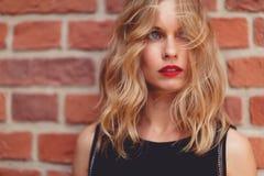 Kaukasische blonde Frau, die hinter Backsteinmauer steht und weg schaut Stockbild