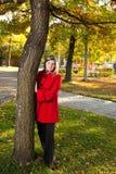 Kaukasische blonde Frau im roten Mantel am Herbstpark, der nahe a steht Stockbild