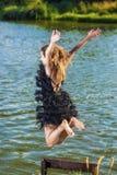 Kaukasische blonde Frau im sexy Kleid, das nahe Wasser-Ufer springt Lizenzfreies Stockfoto