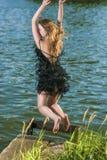 Kaukasische blonde Frau im sexy Kleid, das nahe Wasser-Ufer springt Lizenzfreie Stockfotografie