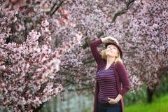 Kaukasische blonde Frau mit dem langen Haar im nahen blühenden Baum des purpurroten Fedorahutes Stockfotos