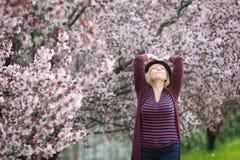 Kaukasische blonde Frau mit dem langen Haar im nahen blühenden Baum des purpurroten Fedorahutes, schauend im Himmel, glücklich Lizenzfreie Stockbilder