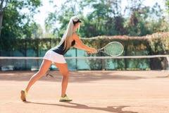 Kaukasische blonde Frau spielt Tennis das im Freien Ansicht von der Rückseite Stockbild