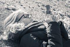 Kaukasische blonde Jugendliche in der schwarzen Jacke, die in Park legt Stockbilder