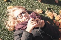 Kaukasische blonde Jugendliche, die in herbstlichen Park legt Stockbilder