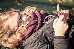 Kaukasische blonde Jugendliche, die in herbstlichen Park legt Lizenzfreies Stockfoto