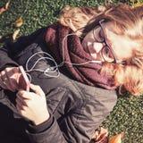 Kaukasische blonde Jugendliche, die in herbstlichen Park legt Stockfotografie