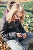 Kaukasische blonde Jugendliche mit Mobiltelefon Lizenzfreie Stockfotos