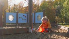 Kaukasische blonde peuterspelen in zandkuil met stuk speelgoed auto Licht erachter stock videobeelden