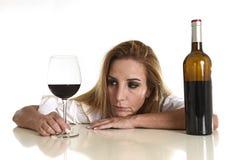 Kaukasische blonde vergeudete deprimierte alkoholische Frau, die Rotweinglasalkoholsucht trinkt Lizenzfreie Stockfotos