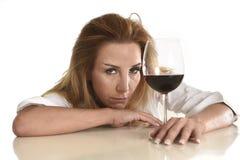 Kaukasische blonde vergeudete deprimierte alkoholische Frau, die Rotweinglasalkoholsucht trinkt Stockfotos