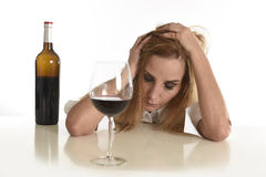 Kaukasische blonde vergeudete deprimierte alkoholische Frau, die Rotweinglasalkoholsucht trinkt Stockfotografie