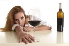 Kaukasische blonde vergeudete deprimierte alkoholische Frau, die Rotweinglasalkoholsucht trinkt Stockfoto