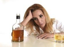 Kaukasische blonde vergeudete und niedergedrückte alkoholische Frau, die Glasunordentliches des schottischen Whiskys getrunken tr Stockbilder