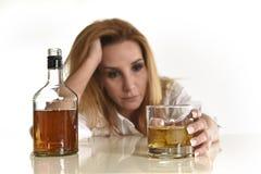 Kaukasische blonde vergeudete und niedergedrückte alkoholische Frau, die Glasunordentliches des schottischen Whiskys getrunken tr Stockbild