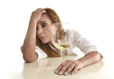 Kaukasische blonde vergeudete und niedergedrückte alkoholische Frau, die Weißweinglashoffnungsloses getrunken trinkt Lizenzfreie Stockfotografie
