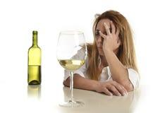 Kaukasische blonde verspilde en gedeprimeerde alcoholische vrouw die witte wijnglas gedronken kater drinken royalty-vrije stock fotografie