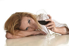 Kaukasische blonde verspilde gedeprimeerde alcoholische vrouw die de alcoholverslaving drinken van het rode wijnglas royalty-vrije stock fotografie