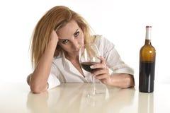 Kaukasische blonde verspilde gedeprimeerde alcoholische vrouw die de alcoholverslaving drinken van het rode wijnglas stock afbeeldingen