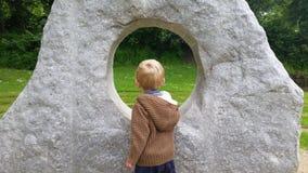 Kaukasische Blondejongen die door beeldhouwwerk kijken Stock Foto